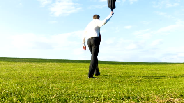 Businessman throwing his jacket off as he walks over a hill video