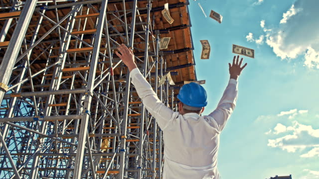 SLO MO Businessman throwing money at the construction site video