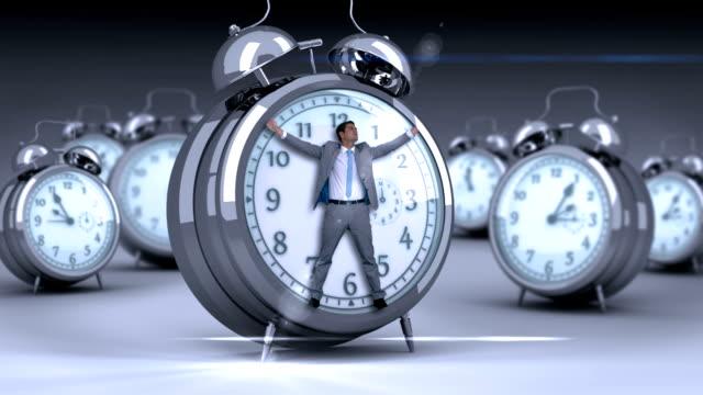 Businessman tied up on alarm clock video
