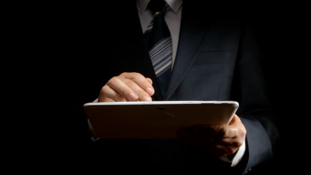 Businessman touches on white tablet PC in hands video