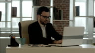 Businessman typing on his keyboard funny glasses video