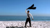 Businessman undressing and throwing his jacket on the beach video
