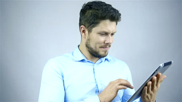 Businessman using a tablet computer - isolated over a grey background video