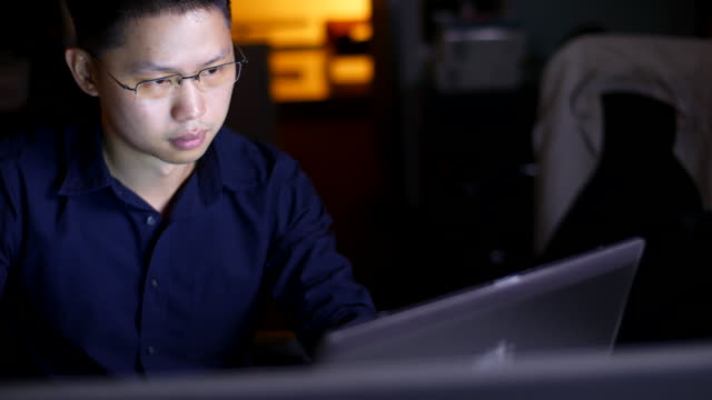 Businessman using computer in office at night video