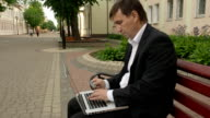 Businessman using his laptop to purchase something online with his credit card video