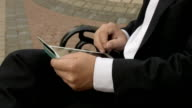 Businessman using his tablet PC to purchase something online with his credit card video