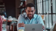 Businessman Using Laptop At Desk In Busy Office Shot On R3D video