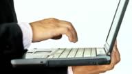 Businessman using laptop while walking video