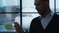 Businessman Using Mobile Phone at the Departure Lounge in the Airport. video