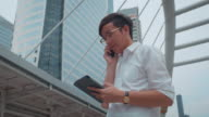 Businessman using smart phone and Digital Tablet urban scene video