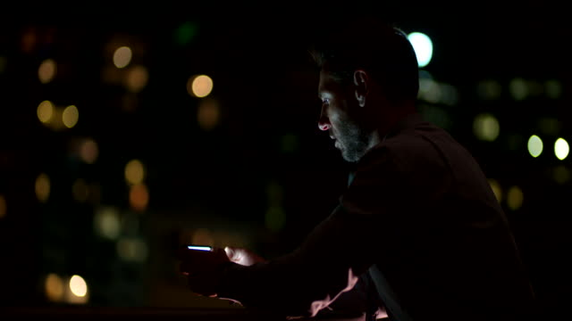 Businessman using smart phone on balcony and enjoying cityscape video