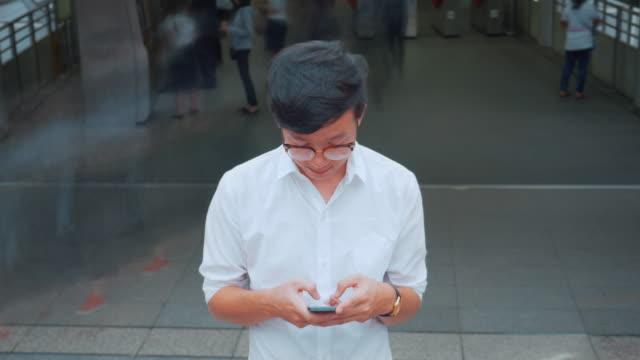 Businessman using smart phone urban scene video