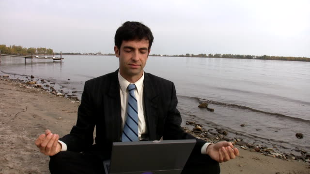 Businessman w/ laptop meditates at the beach. video