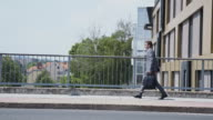 Businessman walking across the bridge in city video