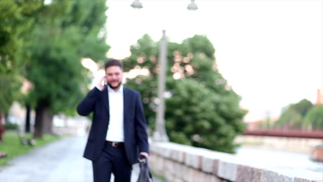 Businessman walking and talking on the phone video