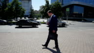 Businessman walking in the street to work. Slow motion video