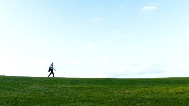 Businessman walking on a hill video