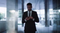 Businessman Walking on Streets of Business District and using Mobile Phone video