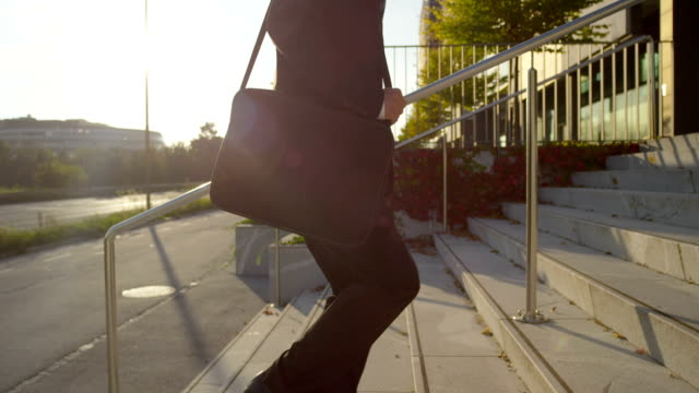 SLOW MOTION: Businessman walking up the stairs towards office building video