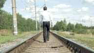 Businessman walks along the rails from camera video