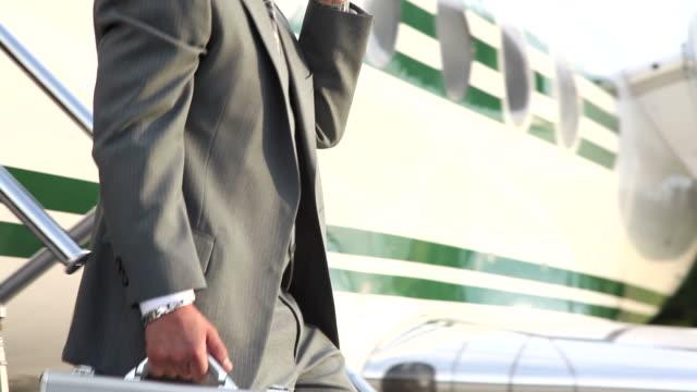 Businessman walks off jet talking on cell phone video