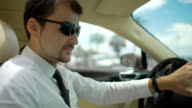 Businessman wearing sunglasses driving expensive automobile, transportation video