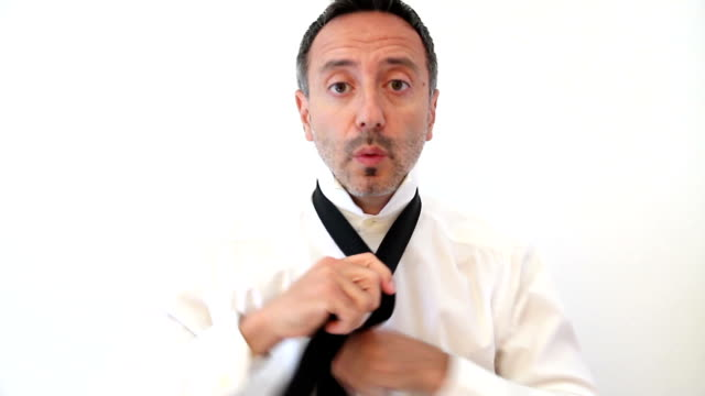 Businessman whistling while puts on a necktie video