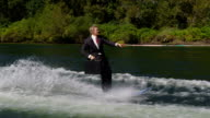 Businessman with briefcase water skiing to work, slow motion video