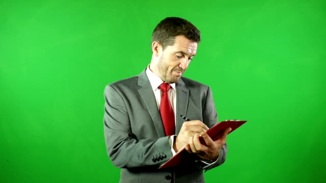 Businessman with clipboard in front of Green Screen video