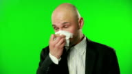 Businessman with flu blowing nose in tissue video