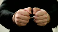 Businessman with handcuffs showing money. video