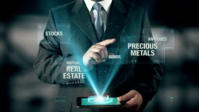 Businessman with Investment concept choose Precious Metals from Bonds Mutual Funds Antiques Stocks Real Estate using digital tablet video