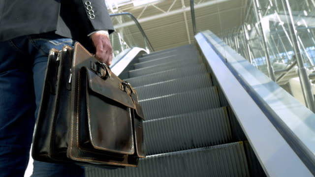 Businessman with leather briefcase riding on escalator video