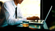 Businessman with modern tablet computer drinking coffee at the cafe video