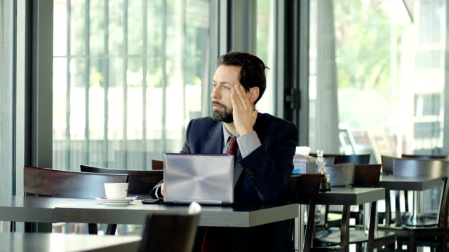businessman with problems on work: sitting alone in a cafè video