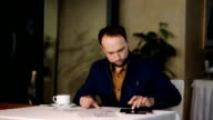 Businessman with tablet computer calculating data on smartphone in cafe video