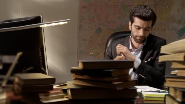 Businessman working and exploring books in the working room. Shot on RED EPIC Cinema Camera. video