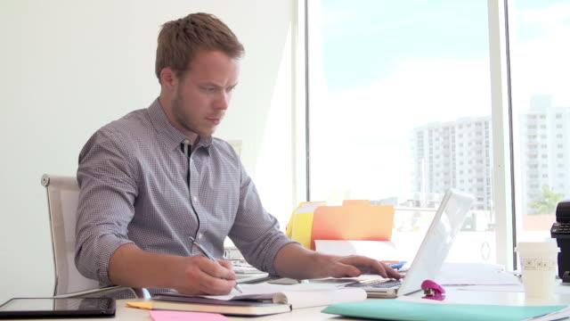 Businessman Working At Desk In Design Studio Answering Phone video