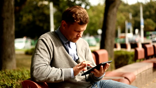 Businessman working on tablet computer by the street video