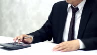 Businessman working with data sheet and using calculator video