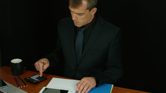 Businessman Writing A Report Gathering Data From A Tablet. video