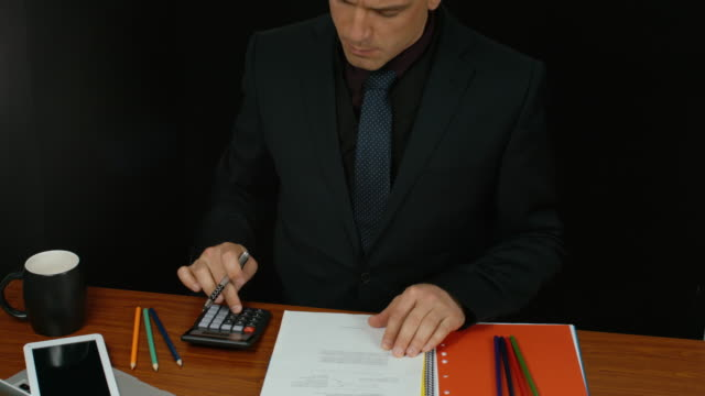 Businessman Writing A Report Using A Calculator. video