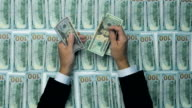 A businessman's hands counting hundred US dollar bills at a table. Dollars background video