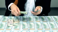 A businessman's hands counting US dollar bills and put them on the table. Money background video