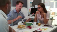 Businessmen And Businesswoman Having Working Lunch In Office video