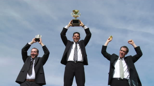 Businessmen celebrating with trophies video