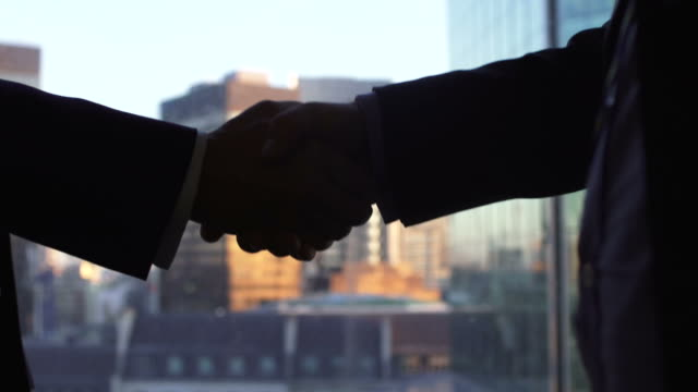 Businessmen Handshake with City Buildings Behind video