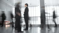 HD TIME-LAPSE: Businessmen Having Discussion In Busy Corridor video