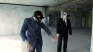 Businessmen in oculus rift watching project of future building video