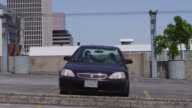 Businessmen jump over car in parking lot, slow motion video